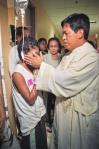 healing priests cancer patient