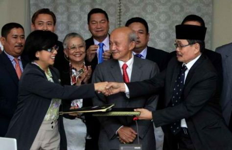 Miriam Coronel-Ferrer, front left, chairperson of Philippine Government Peace Panel, and Mohagher Iqbal, front right, chief negotiator for the Moro National Liberation Front (MNLF), exchange signed documents as Malaysian facilitator Abdul Ghafar Tengku Mohamed, front center, witnesses after the 43rd GPH-MILF Exploratory Talks in Kuala Lumpur, Malaysia, Saturday, Jan. 25, 2014. The Philippine government and the country's largest Muslim rebel group completed talks Saturday on a deal to end four decades of fighting that has killed tens of thousands of people and helped foster Islamic extremism in Southeast Asia. Photo: Lai Seng Sin, AP