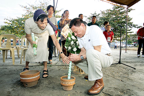 Mayor Rodrigo R. Duterte, together with Sister Jo Bacaltos, lights up a candle and offers a prayer for the victims of the old Davao City Airport bombing in Sasa during the tragic incident's 11th anniversary commemoration Tuesday afternoon. Lean Daval Jr./EDGE DAVAO