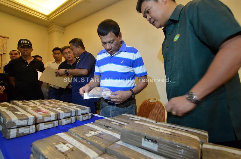 Davao City Mayor Rodrigo Duterte shows recovered cocaine bricks