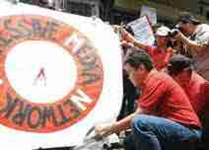 BROADCASTER REY FABE SETS FIRE, IN THE 2012 STRIKE, TO A PLACARD BEARING THE RMN LOGO