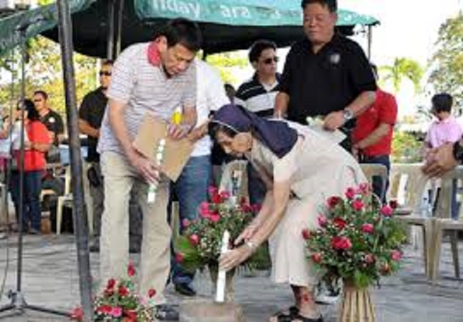 SAD RITUAL. Mayor Rodrigo Duterte offers flowers and lights candles at the 2003 site of bombings, in what has become a yearly ritual to commemorate the carnage that killed dozens of people and wounded nearly 200.