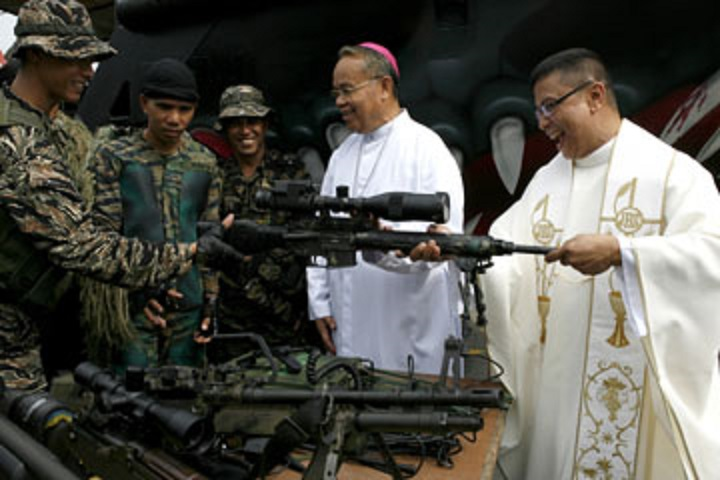 Priests check the firearms of Marines who will be sent to Basilan province in southern Philippines during the 110th founding anniversary of the Philippine Navy in Manila